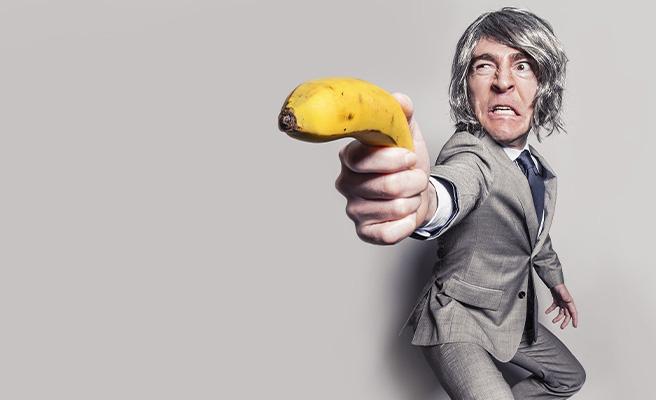A angry man uses a banana as a gun
