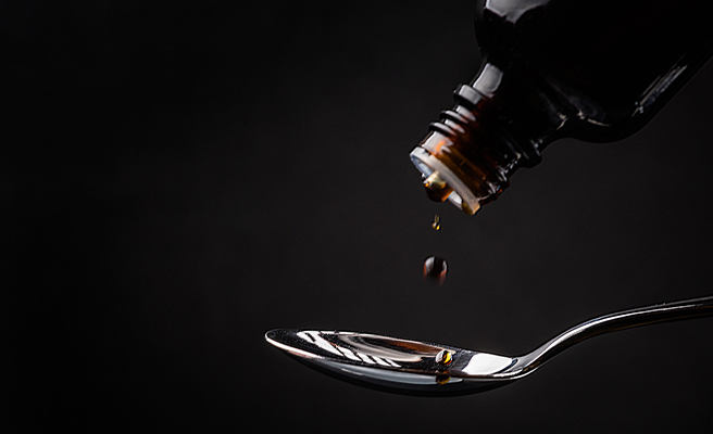 Pouring a spoonful of medicine