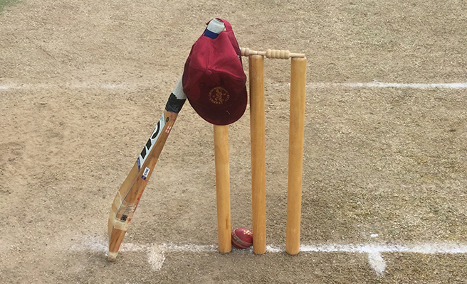 A cricket bat, ball, hat and stumps