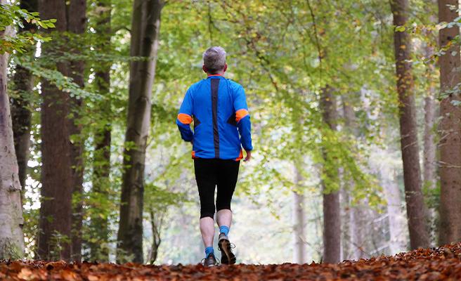 An older man runs in a wood