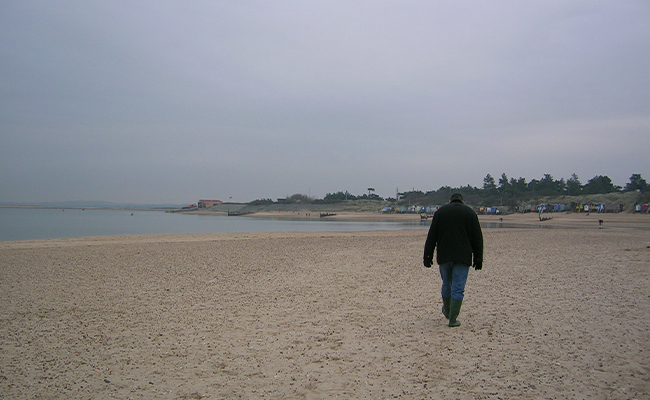 Man walks sadly on beach